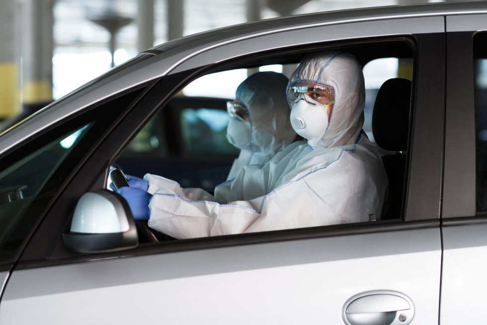 Quarantine time. People in coronavirus protective suits driving a car, pandemic concept